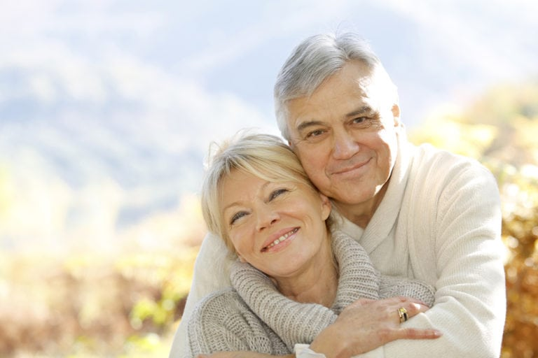 elderly man and woman holding each other smiling